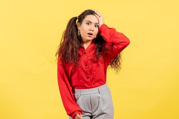 Vista frontale ragazza in camicetta rossa con la faccia dispiaciuta su sfondo giallo sentimento femminile bambino bambina ragazza emozione giovanile