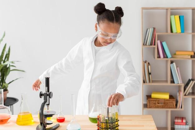 Vista frontale dello scienziato della ragazza in camice da laboratorio con pozioni e microscopio