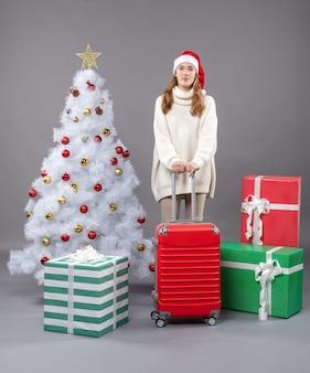 크리스마스 트리와 선물 근처에 서있는 산타 모자를 쓰고 전면보기 어린 소녀