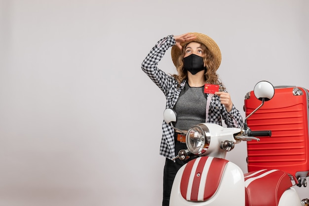 赤い原付の近くに立ってカードを保持している黒いマスクを持つ正面少女
