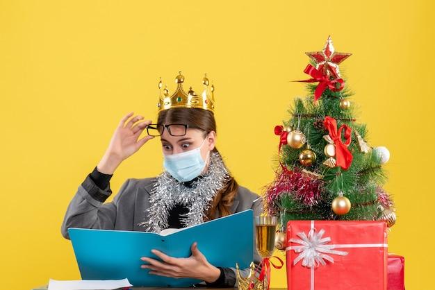 Молодая девушка с короной, снимающая очки, рождественская елка и подарочный коктейль, вид спереди
