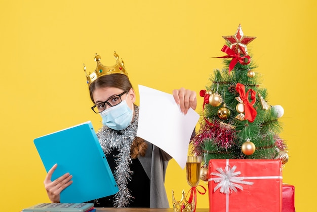 Вид спереди молодая девушка с короной, показывающая документы, рождественское дерево и коктейль подарков