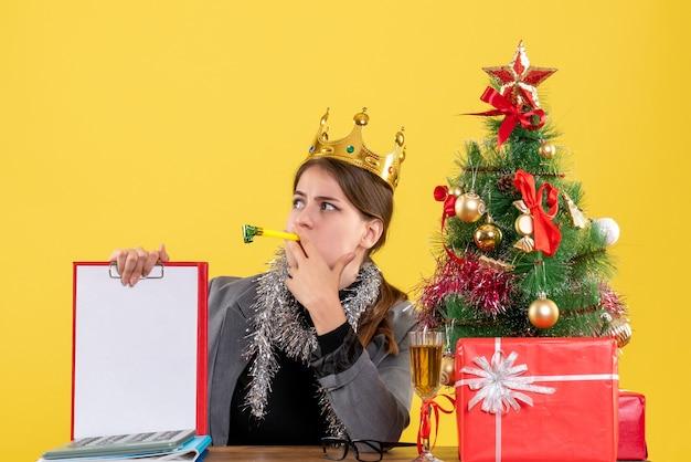 Вид спереди молодая девушка с короной, сидящая за столом, держащая документ, рождественскую елку и подарочный коктейль