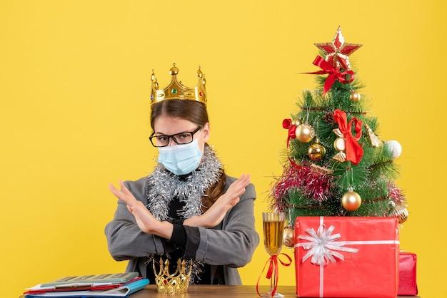 Вид спереди молодая девушка с короной в маске и очках, скрестив руки, рождественская елка и подарочный коктейль