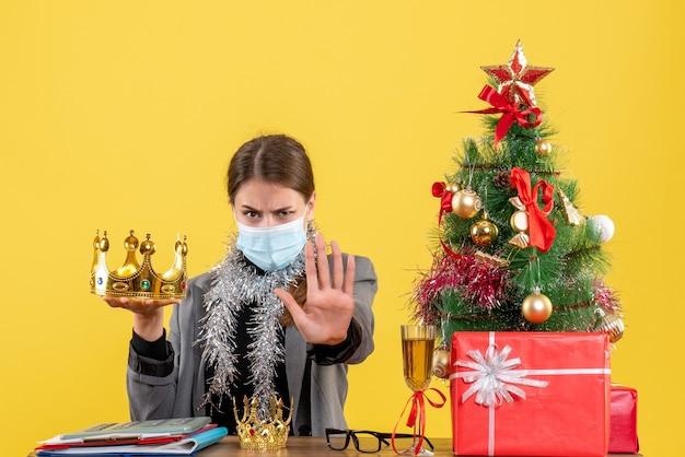 Вид спереди молодая девушка с короной в маске рождественская елка и подарочный коктейль