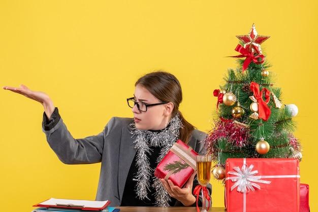 Ragazza di vista frontale con gli occhiali che si siedono alla tavola che mostra qualcosa albero di natale e cocktail dei regali
