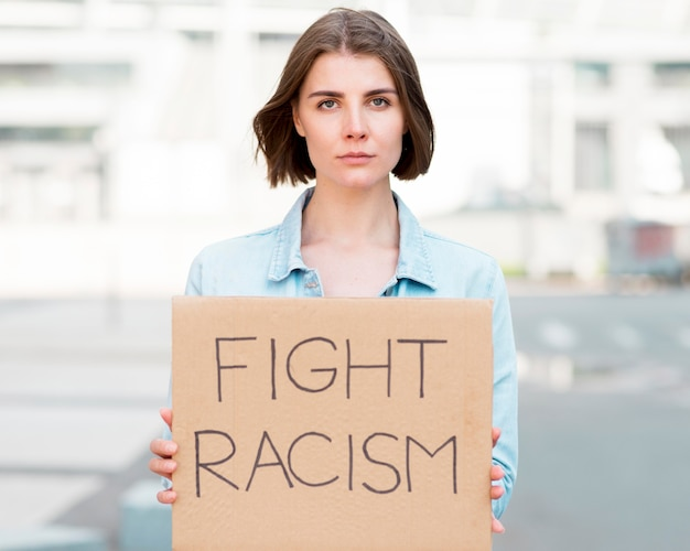 Front view young girl with fight racism quote on cardboard