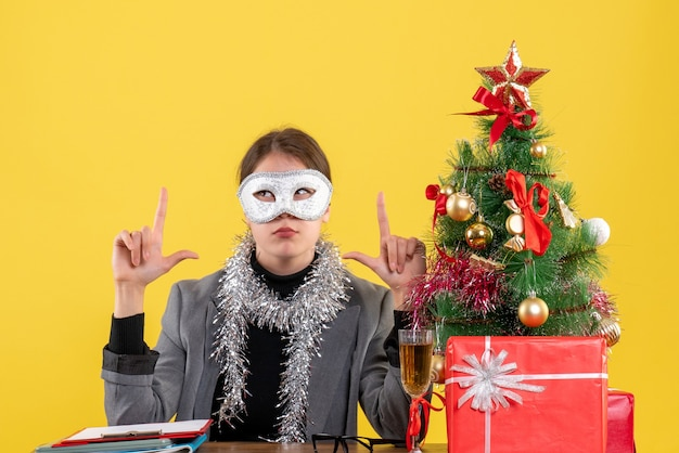 Front view young girl with mask sitting at the table showing something with fingers xmas tree and gifts cocktail