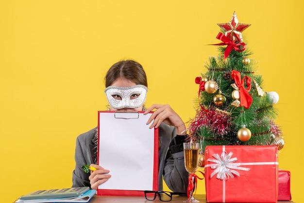 Giovane ragazza di vista frontale con la maschera di travestimento che si siede al tavolo gholding documento albero di natale e regali cocktail