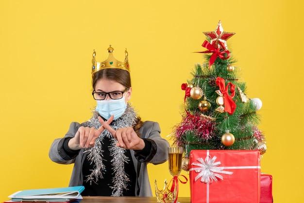 Вид спереди молодая девушка с медицинской маской, скрестив пальцы, рождественская елка и подарочный коктейль