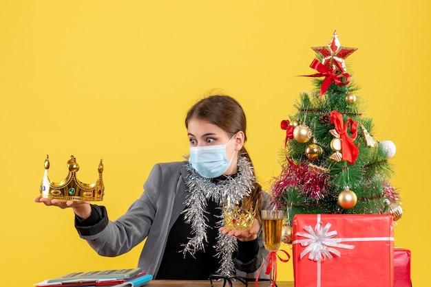Молодая девушка с медицинской маской, глядя на корону рождественской елки и подарочный коктейль, вид спереди