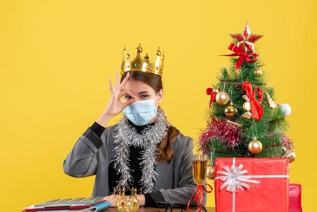 Ragazza di vista frontale con mascherina medica che fa segno okey davanti al suo cocktail di albero di natale e regali dell'occhio