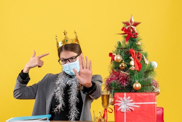 Вид спереди молодая девушка с медицинской маской, показывающая свою корону, рождественское дерево и подарочный коктейль