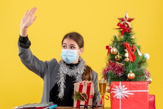 Ragazza di vista frontale con mascherina medica che si siede al tavolo salutando qualcuno albero di natale e regali cocktail Foto Gratuite