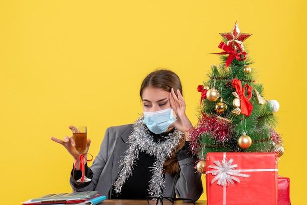 Giovane ragazza di vista frontale con mascherina medica che si siede al tavolo che indica con il dito