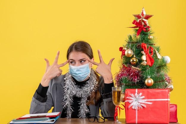 Giovane ragazza di vista frontale con mascherina medica che si siede al tavolo che mette le dita