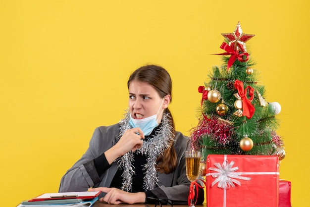 Giovane ragazza di vista frontale con mascherina medica che si siede al tavolo che toglie la sua maschera albero di natale e regali cocktail