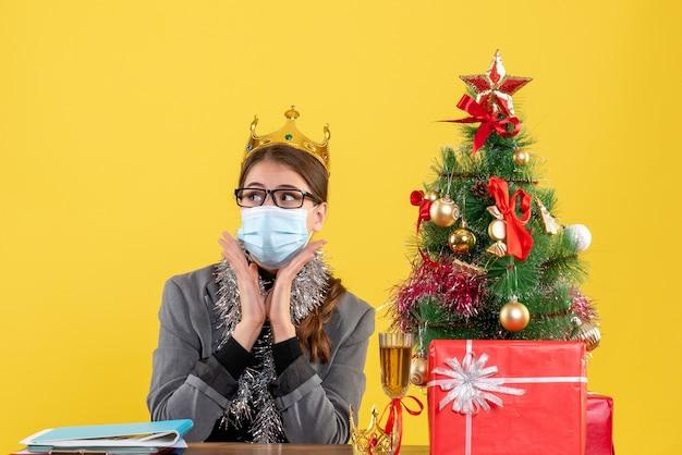 Ragazza di vista frontale con mascherina medica che si siede al cocktail dell'albero di natale e dei regali della tavola