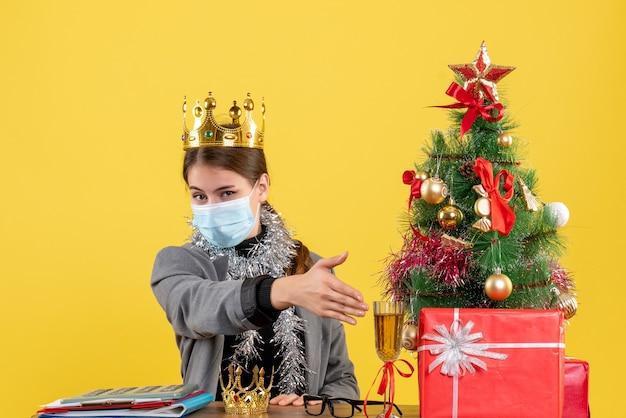 Вид спереди молодая девушка с медицинской маской в короне, протягивающая руку рождественскому дереву и подарочному коктейлю