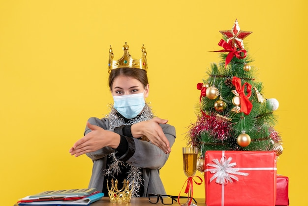 손에 크리스마스 트리와 선물 칵테일을주는 왕관을 쓰고 의료 마스크와 전면보기 어린 소녀