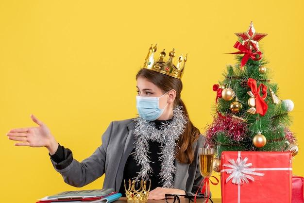 Ragazza di vista frontale con la corona da portare della mascherina medica che dà il suo cocktail dell'albero di natale e dei regali della mano