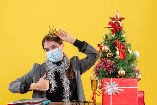 Ragazza di vista frontale con la parte superiore d'uso della mascherina medica che fa pollice sul cocktail dell'albero di natale del segno e dei regali