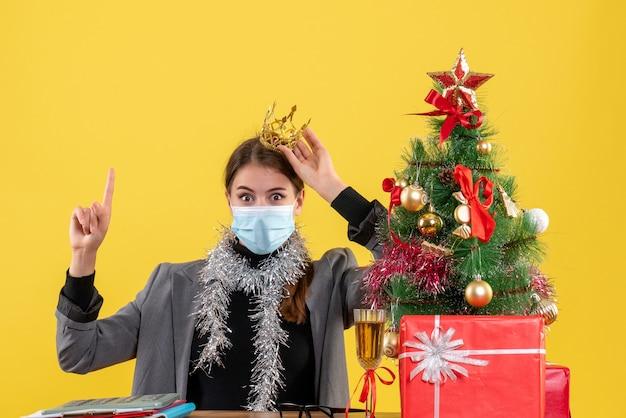 Giovane ragazza di vista frontale con mascherina medica che indossa la corona che indica con il dito sull'albero di natale e cocktail dei regali