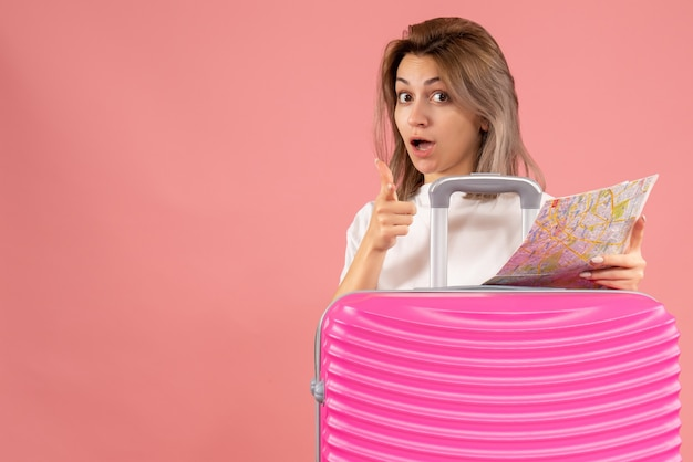 Vista frontale ragazza con valigia rosa che tiene mappa che punta il dito davanti
