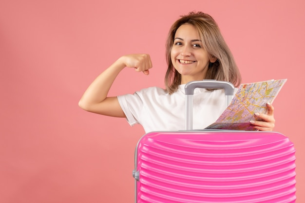 腕の筋肉を示す地図を保持しているピンクのスーツケースを持つ正面少女