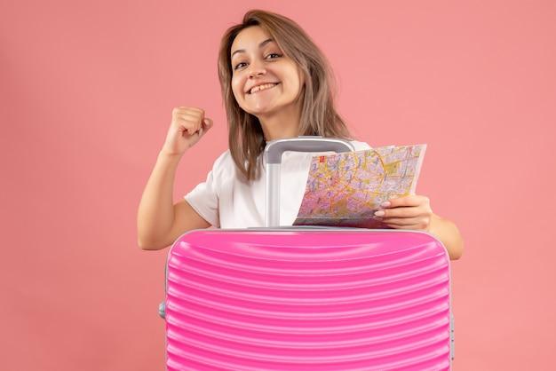 彼女の幸せを示す地図を保持しているピンクのスーツケースを持つ若い女の子の正面図