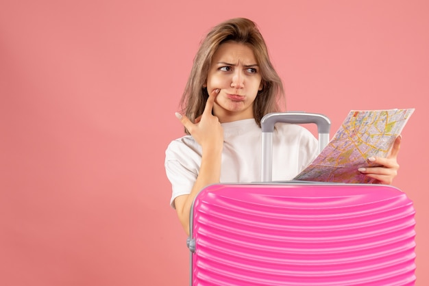 何かを考えて地図を保持しているピンクのスーツケースを持つ若い女の子の正面図