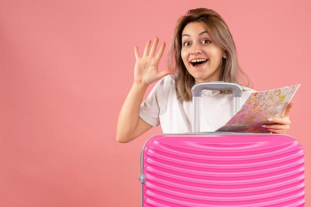 手を振って地図を持ってピンクのスーツケースを持つ若い女の子の正面図