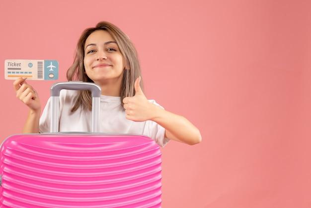 親指をあきらめて飛行機のチケットを保持しているピンクのスーツケースを持つ正面少女