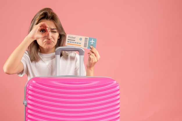 手双眼鏡を作るチケットを保持しているピンクのスーツケースを持つ正面少女