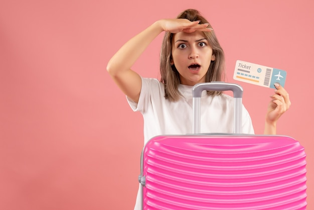 Молодая девушка с розовым чемоданом и наблюдением за билетом, вид спереди