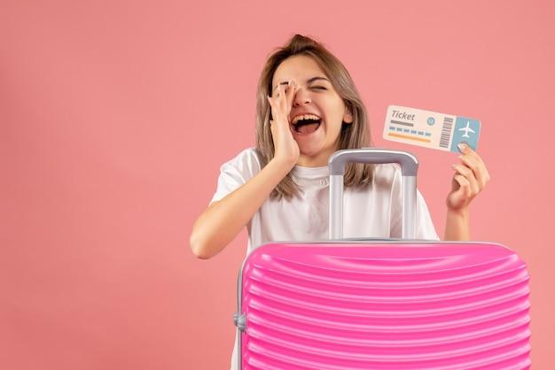 叫んでチケットを保持しているピンクのスーツケースを持つ正面の若い女の子