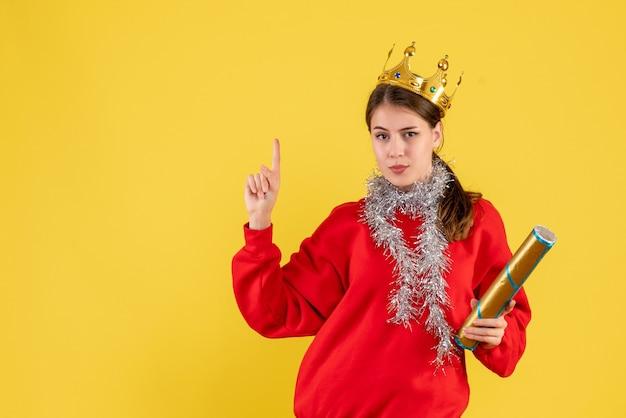 指を上に向けてパーティーポッパーを保持している赤いセーターと正面図の少女