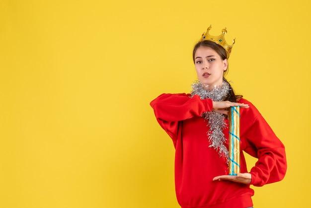 파티 포퍼를 들고 빨간 스웨터와 전면보기 어린 소녀