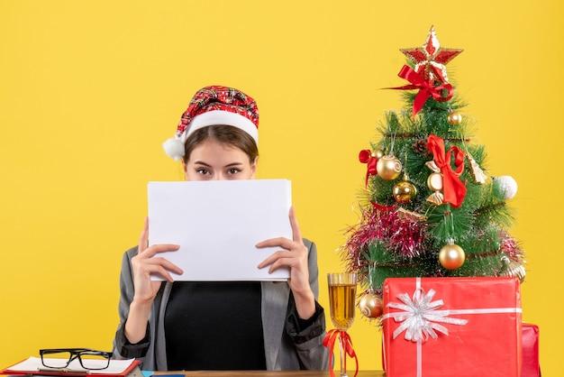 Вид спереди молодая девушка в рождественской шляпе сидит за столом, закрывая лицо документами, рождественской елкой и подарочным коктейлем