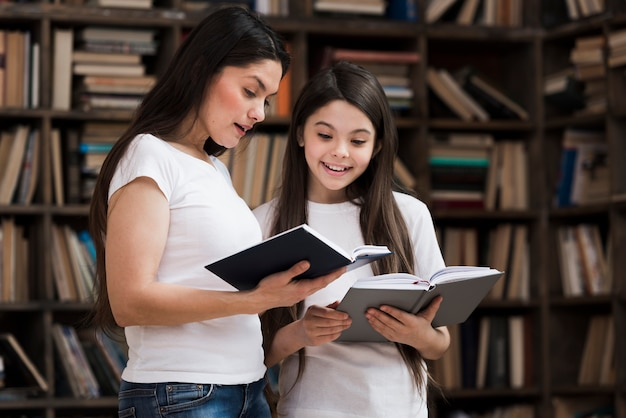 Front view young girl and woman reading books