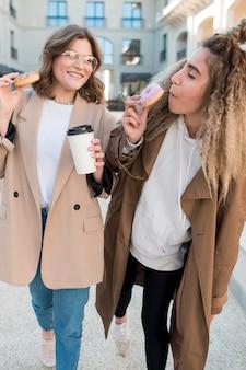 Front view young girls enjoying doughnuts