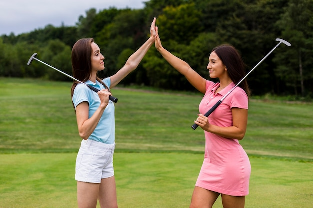Front view of young golfers high fiving