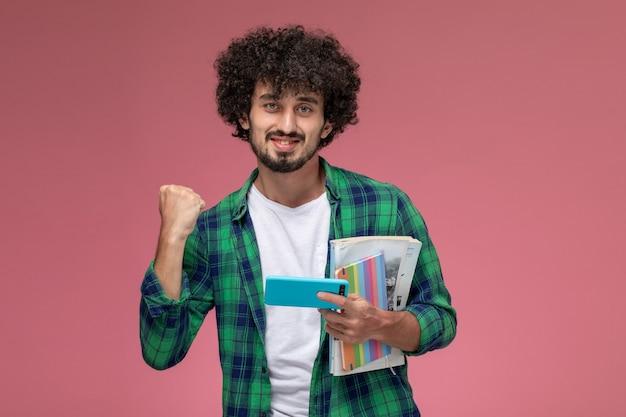 Ragazzo giovane vista frontale che fa gesto di vittoria su sfondo rosa