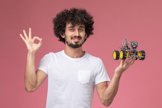 Молодой парень, вид спереди, жестом показывая роботизированные инновации