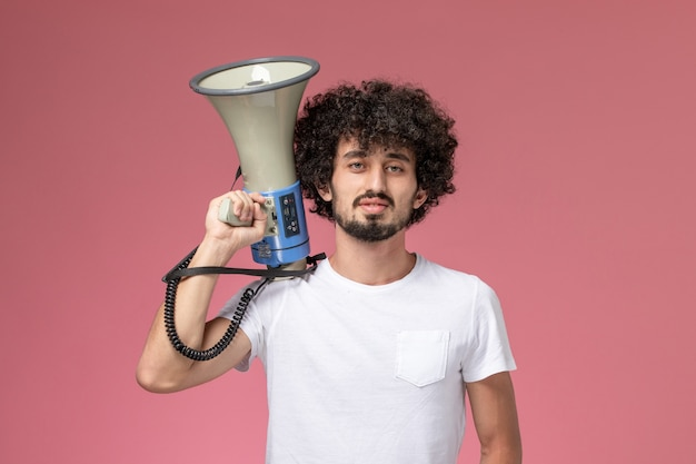 Вид спереди молодой парень, держащий микрофон рядом с его головой