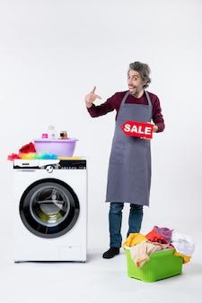 앞치마를 입은 젊은 남자가 흰 벽에 있는 세탁기 근처에서 자신을 가리키는 판매 표지판을 들고 있다