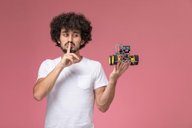 침묵 제스처와 전자 로봇을 계속 보여주는 전면보기 젊은 남자