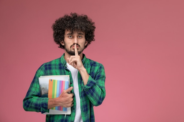 Front view young guy shows keep silent gesture with notebooks