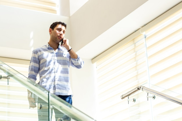 A front view young handsome man in striped shirt talking and discussing work issues on the phone during daytime work activity building