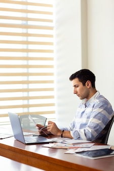 A front view young handsome man in striped shirt working inside conference hall using his silver laptop looking through documents writing down during daytime work activity building